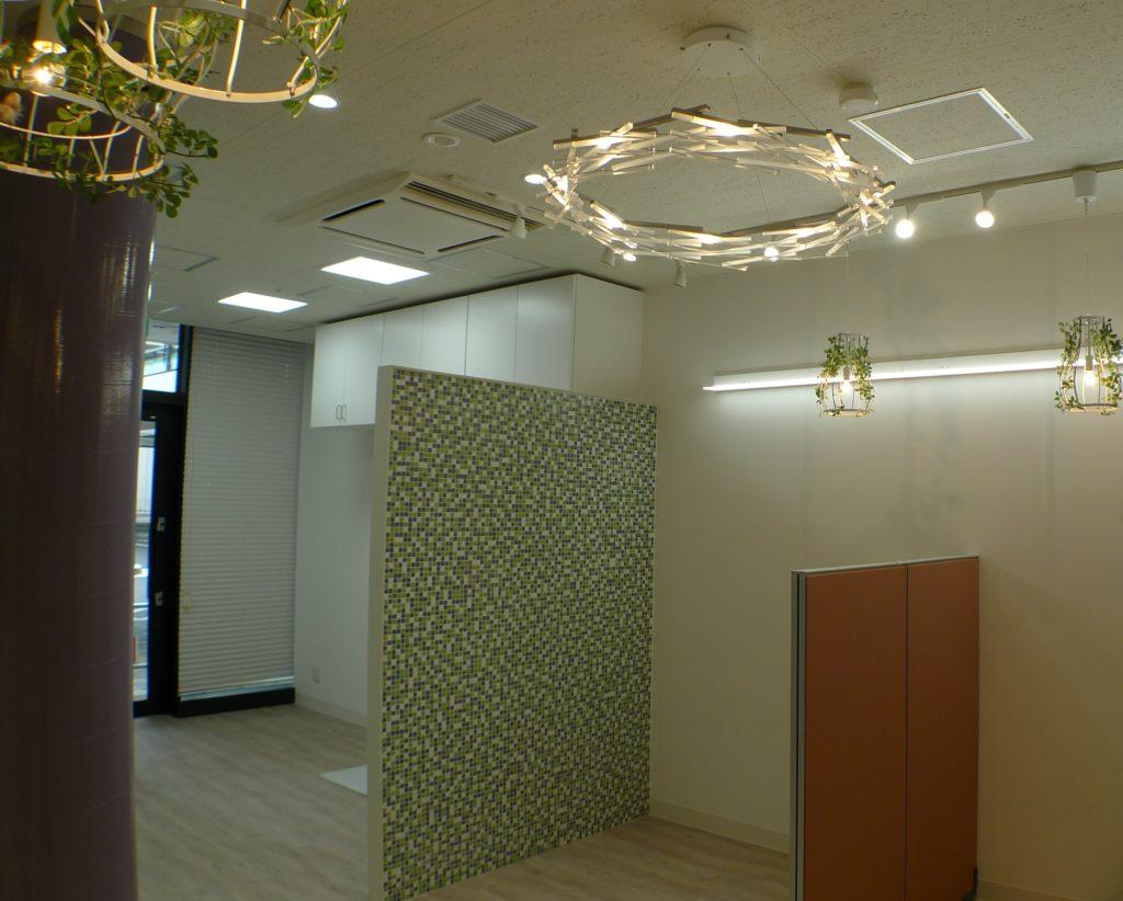 不動産店舗のインテリアデザイン。モザイクタイルと柱、間仕切りパーテーションがアクセントに。カフェのようなオシャレな店舗に仕上がりました。