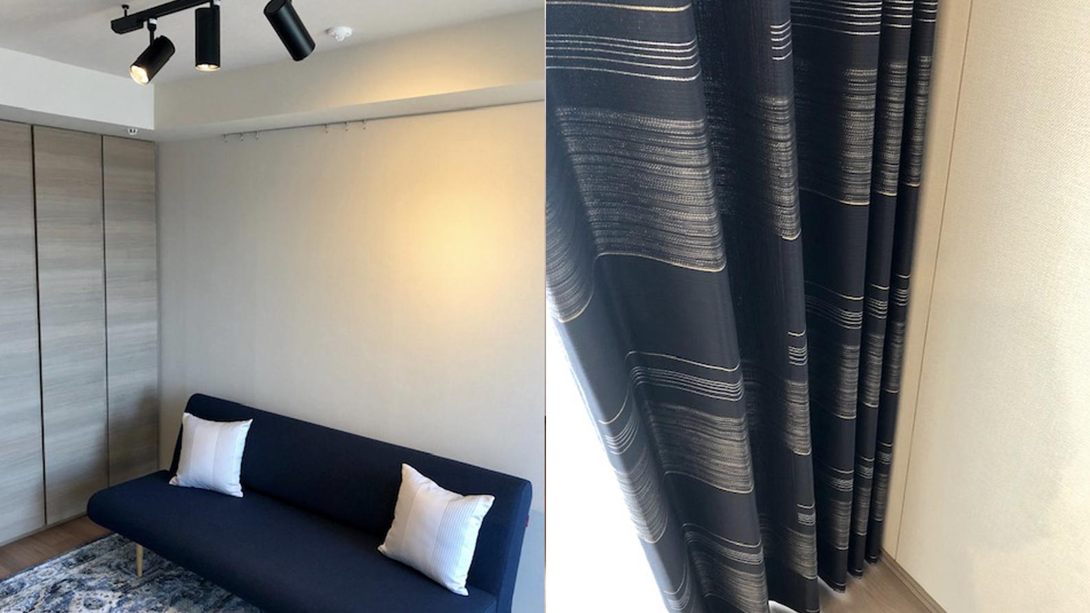 ネイビー×シルバーのカーテンとコーディネートしたソファベッドのあるワンルーム