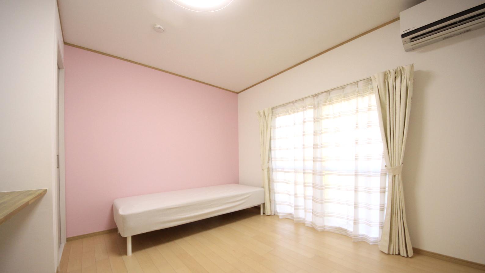 一戸建てシェアハウスのピンク壁紙の明るい居室