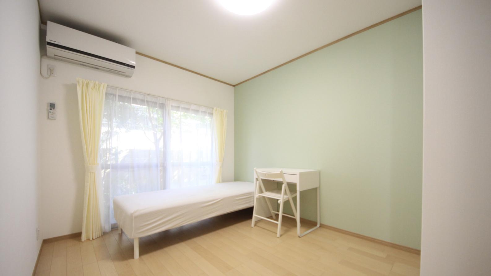 一戸建てシェアハウスのグリーン壁紙の明るい居室