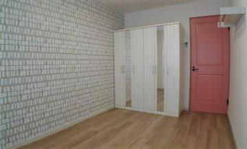 個室にも収納力とアクセントクロス&ドアで明るい空間に